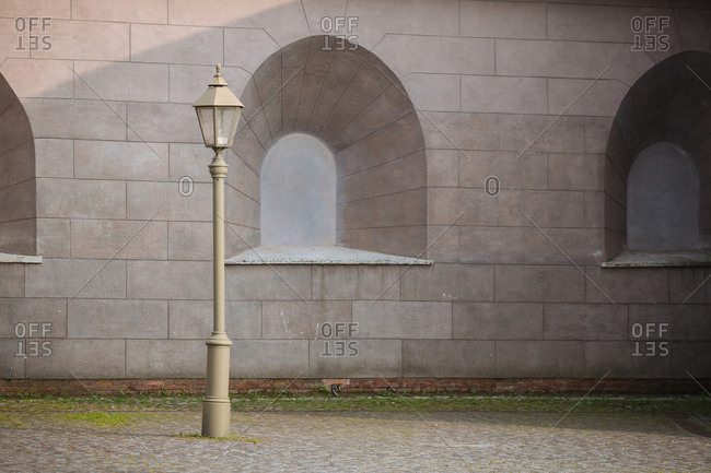 Lamppost by gray stone building