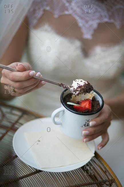 Bride eating dessert from mug