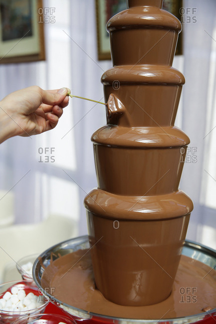 Hand dipping into chocolate fountain