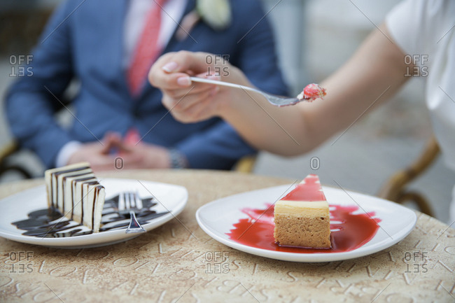 Couple eating cheesecake at wedding