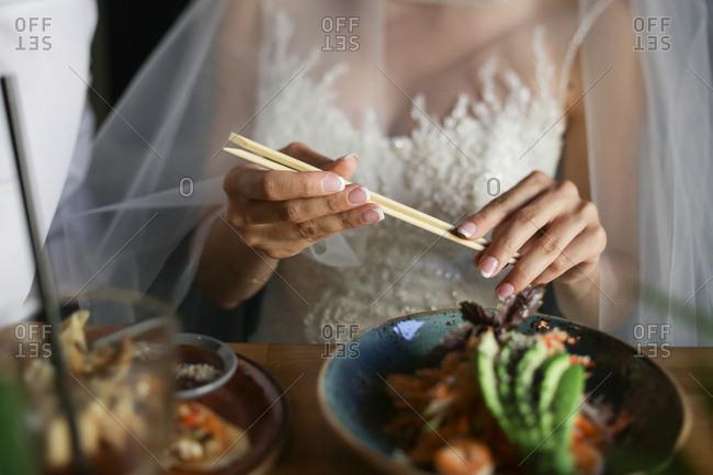 Bride holding chopsticks at dinner
