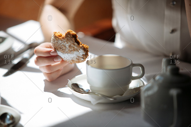 Woman eating cookie with tea