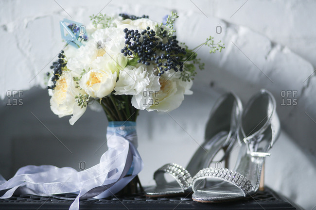 Silver high heels by wedding bouquet