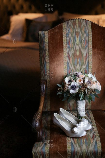 High heel and bouquet on chair