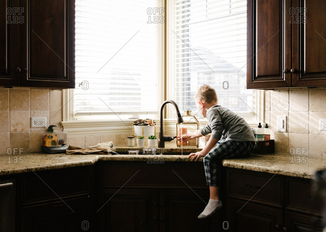 Boy on counter running faucet
