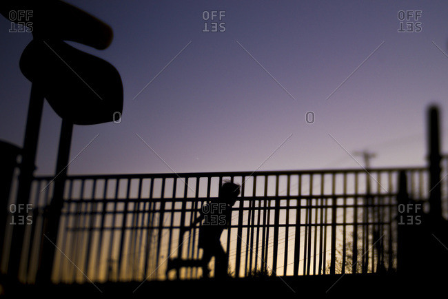 Silhouette of child running between railings at sunset