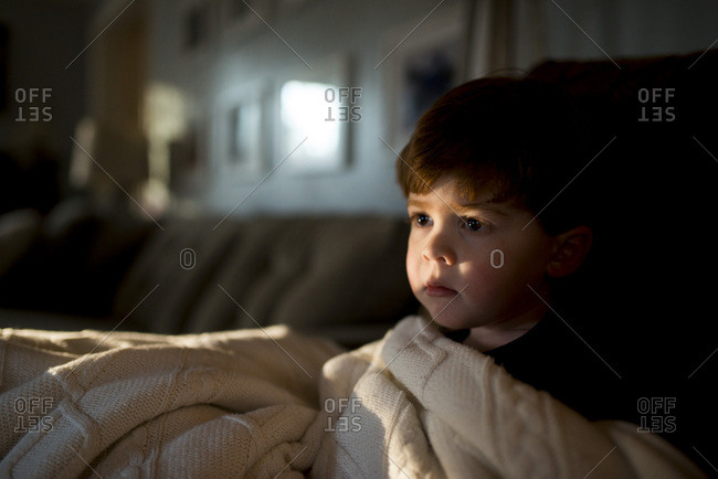 Young boy sitting on sofa wrapped in a blanket