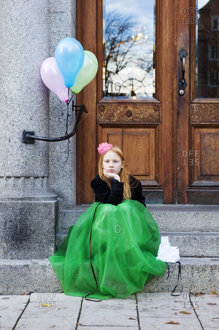 Girl in fancy green gown sitting on steps with balloons