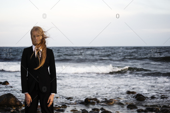 Young woman in menswear standing on beach