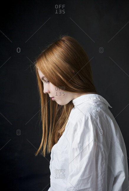 Side view of a teenage girl with long red hair