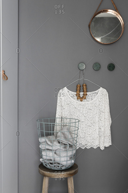 Lacy blouse hanging on wall by wire basket