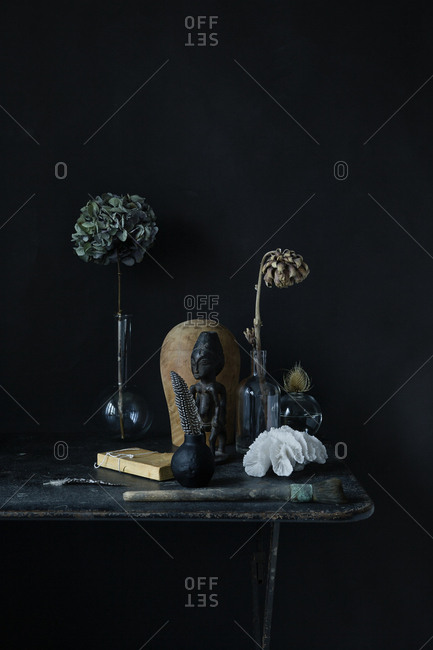 Still life of flowers and an African sculpture