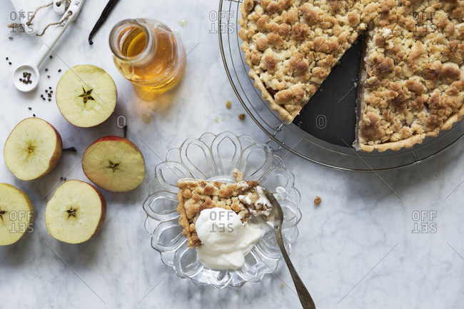 Apple crumble and a slice served on a plate