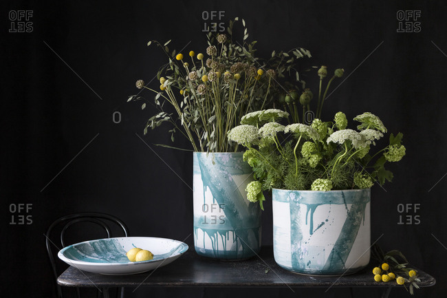 Ceramic vases with floral arrangement on dark background