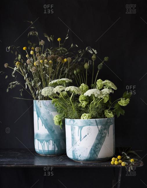 Vases with floral arrangement on dark background