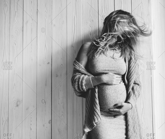 Pregnant woman leaning against a wall holding her belly and turning her head