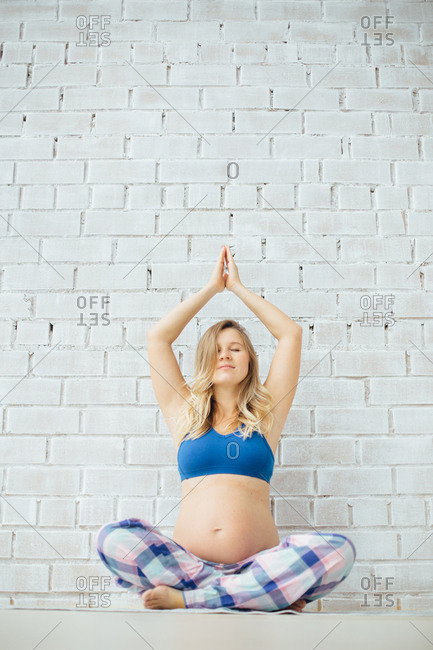 Pregnant woman sitting on the floor in a yoga position