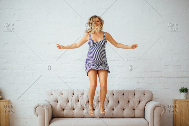 Pregnant woman jumping up and down on a sofa
