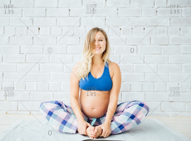 Pregnant woman sitting on a floor doing yoga and smiling