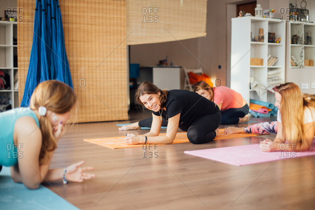 Pregnant women smiling and practicing yoga in a studio