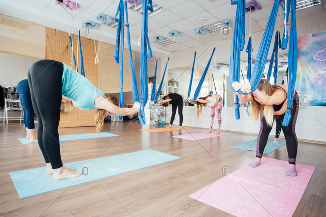 Pregnant women practicing aerial yoga together in a studio