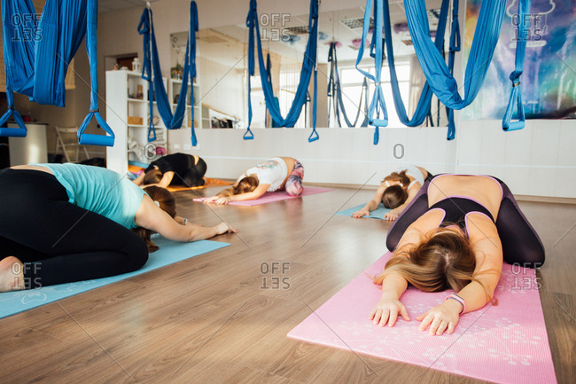 Pregnant women stretching on mats in an aerial yoga studio