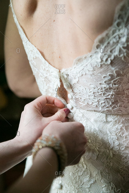 Hands of a woman fastening a bride's gown on her wedding day