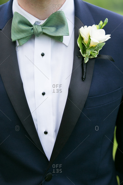 Close-up of a groom with a green bowtie and navy tux