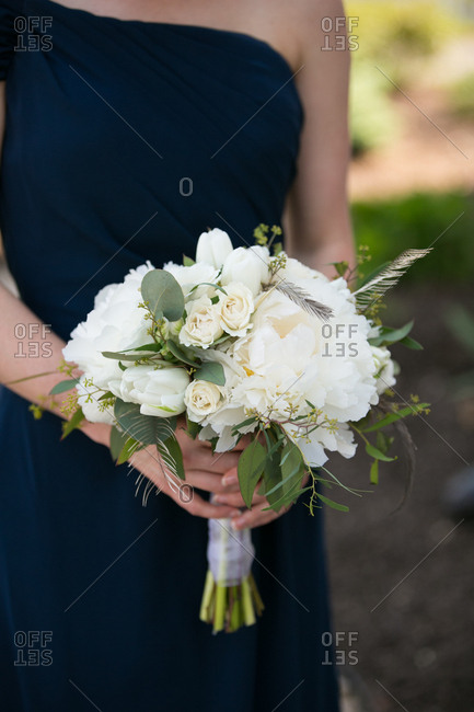 Bridesmaid in a navy blue dress holding a bouquet of white flowers