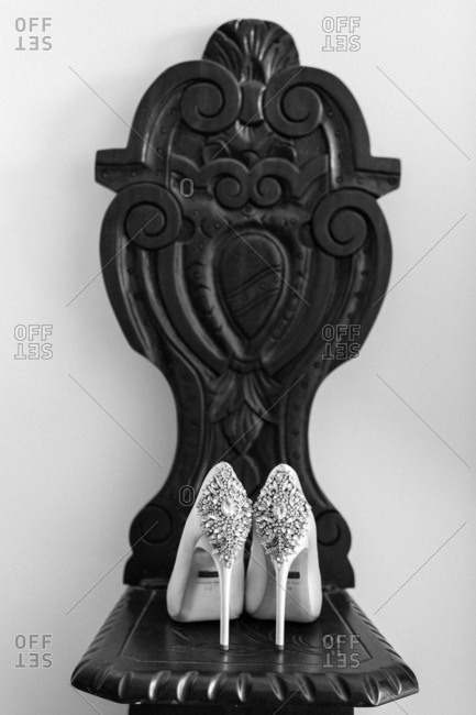 Formal satin shoes with embellished heels on a carved wooden table