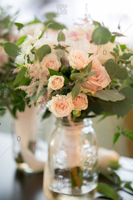 Bouquets of light pink roses in mason jars