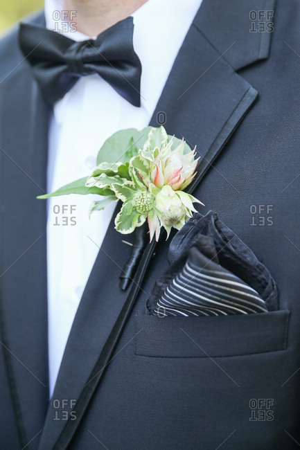 Groom in a black tuxedo with a boutonniere