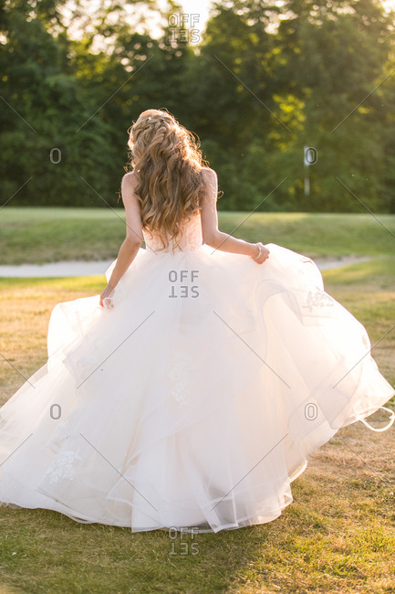 Bride standing on a lawn holding the skirt of her wedding dress