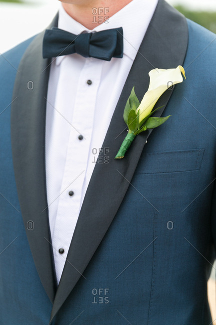 Groom in a navy blue tuxedo with a boutonniere