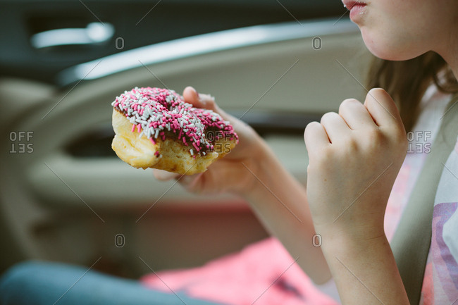 Child eating donut with sprinkles in car