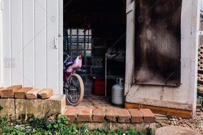 Child's bike parked in barn