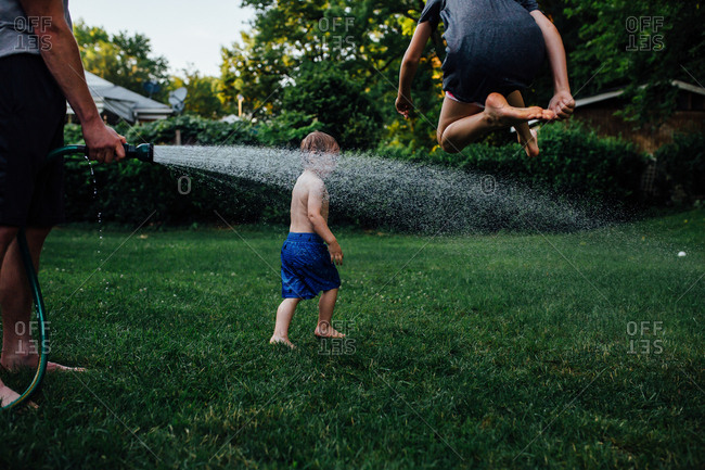 Child leaping above hose spray