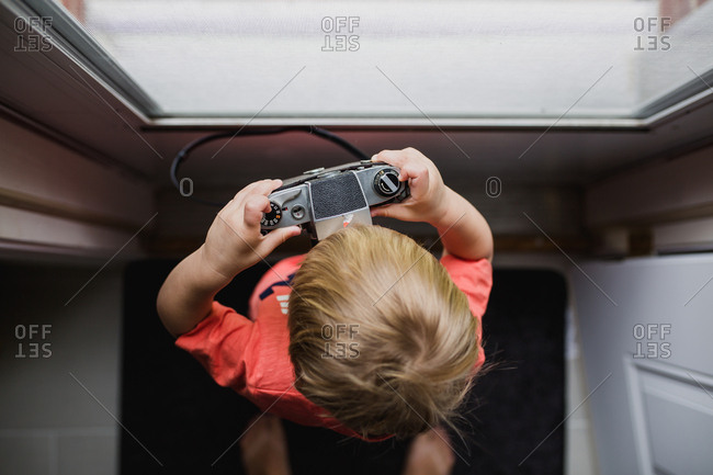 Boy with camera at window