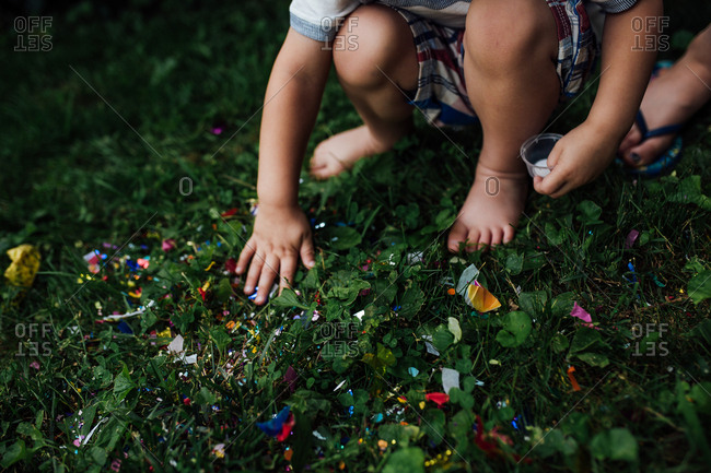 Child with colorful confetti in grass