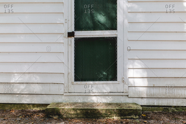 Closed door with chicken wire on farm building