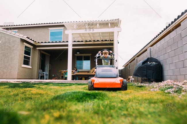 Boy pushing a lawnmower in backyard
