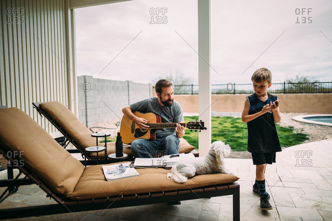Man plays guitar on patio while son and dog listen