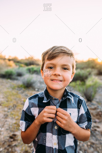 Cute young boy buttoning his shirt in desert landscape