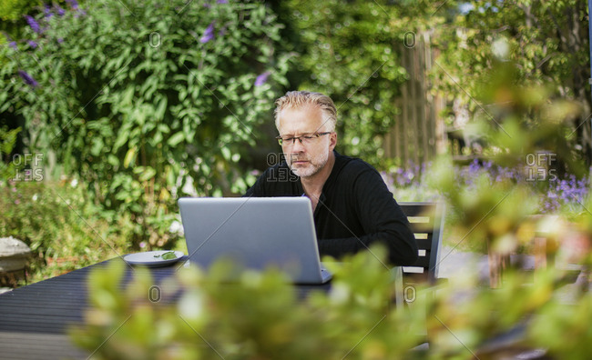 Denmark, Mon, Man working on laptop on patio