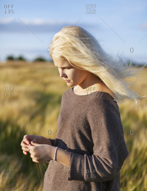 Denmark, Mon, Teenage girl playing with grass