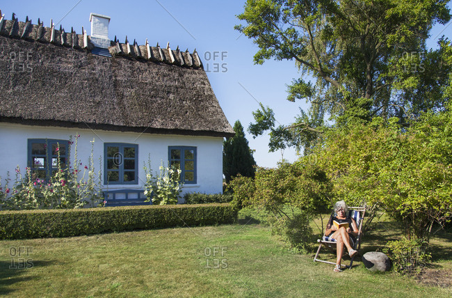 Denmark, Mon, Woman sitting in front of house and reading