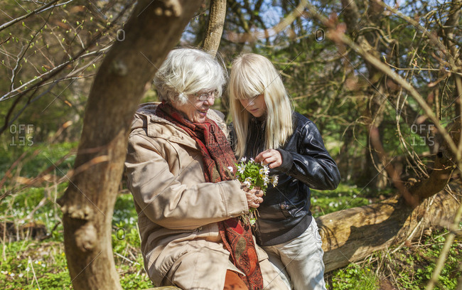 Denmark, Mon, Girl with grandmother looking at flowers