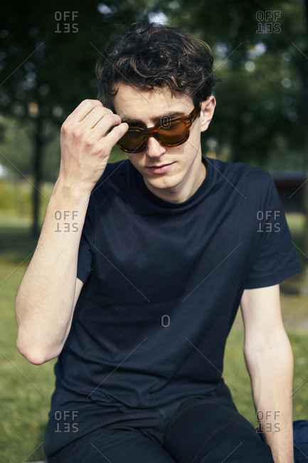 Sweden, Uppland, Man in black and sunglasses sitting in park