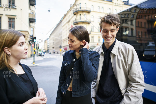 Sweden, Uppland, Stockholm, Kungsholmen, Young people standing in street talking