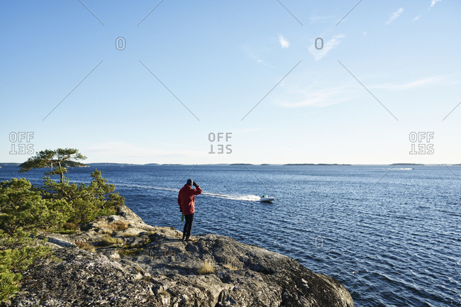 Sweden, Stockholm Archipelago, Varmdo, Bjorno, Man looking at view, motorboat in sea